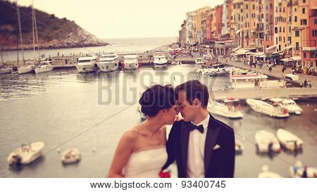 Happy bridal couple near boats