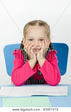 Portrait Of A Pensive Pupil At School Desk