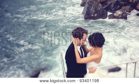 Bride and groom on rocky shore