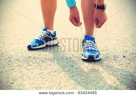 young woman runner tying shoelaces on city bridge road