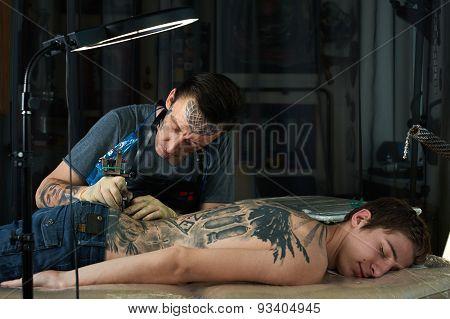 Tattoo Artist Makes A Tattoo On The Back