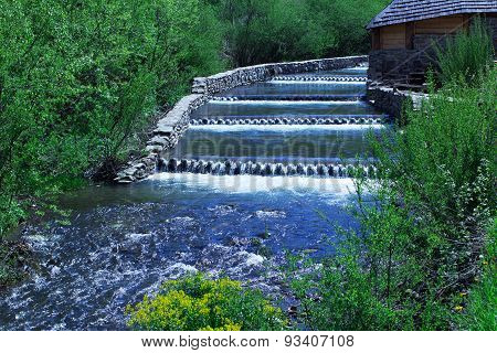 River Cascading Among Green Forest And Wooden House