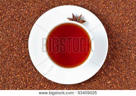White cup of red rooibos South African tea with star anise