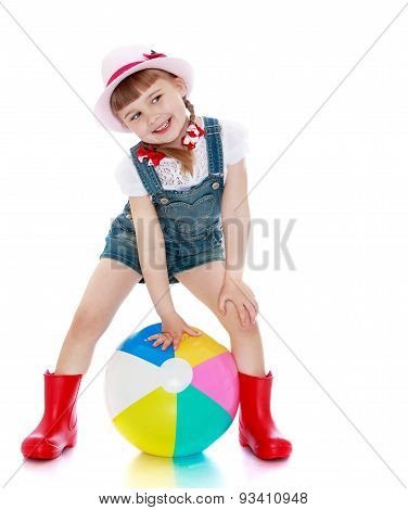 Cheerful girl in shorts, hat and rubber boots playing ball