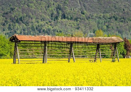 Hayrack Standing In A Field With Mountains In Background