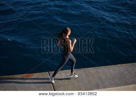 Full length portrait of cute young woman out jogging along the coastline at sunny day