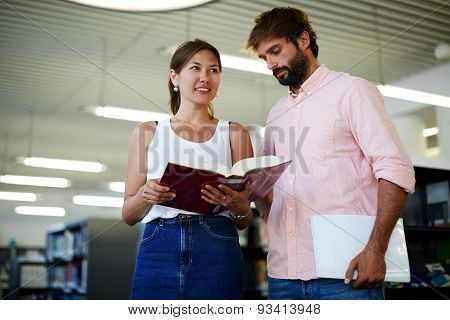 Business colleagues having fun in his hands while standing in modern work space in library