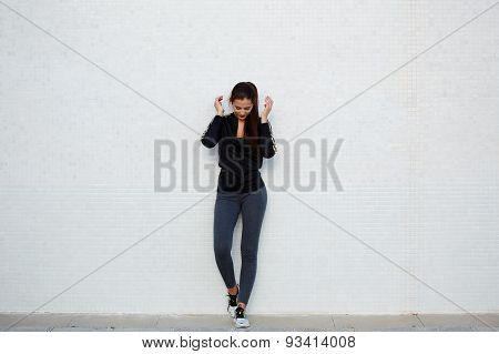 Charming girl with fitness body getting ready for workout outdoors while standing a white background