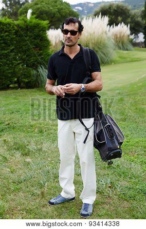 Handsome brunette man in glasses with golf bag on shoulder holding ball in the hands