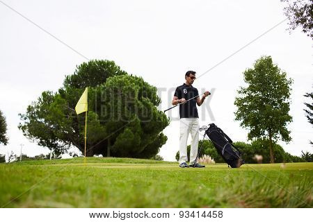 Mature handsome man playing golf at beautiful summer day on green course