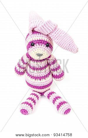 Knitted Rabbit Toy Is Sitting With Knotted Ears