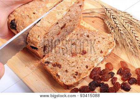 Slicing Fresh Bread, Ears Of Wheat And Raisins