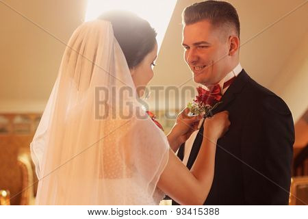 Bride Putting Flower On Her Groom's Chest