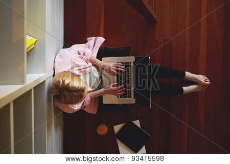 Young female student studying from home with her laptop computer