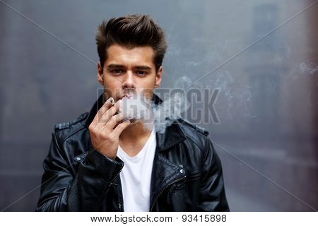 Portrait of a young fashionable man smoking a cigarette with copy space looking to the camera