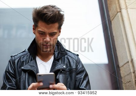 Attractive stylish male student texting message on his cell phone while standing out in the city
