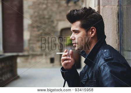 Handsome male model holding cigarette in the hand looking pensive and serious