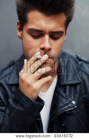 Close up portrait of young charming man with cigarette in his mouth standing on grey background