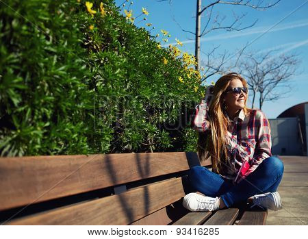 Attractive girl in sunglases relaxing in the spring park while reading book outdoors