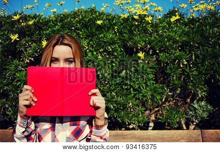 Flirtatious girl covering half face with a book while standing on spring green hedge with flowers