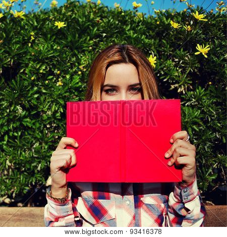 Cute female covering half face with a book while standing on spring green hedge with flowers