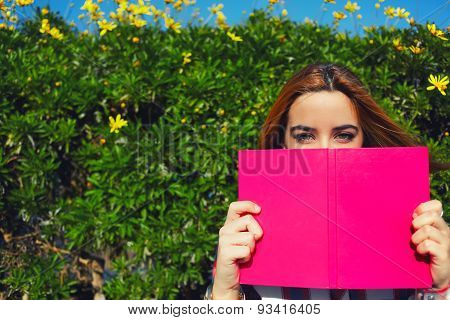 Portrait of charming young woman with pink book held up close to her face