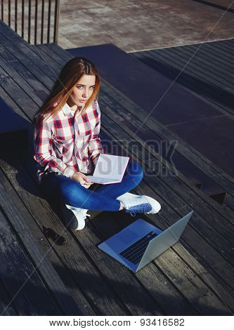 A shot of caucasian college student reading the book while working on laptop computer at campus