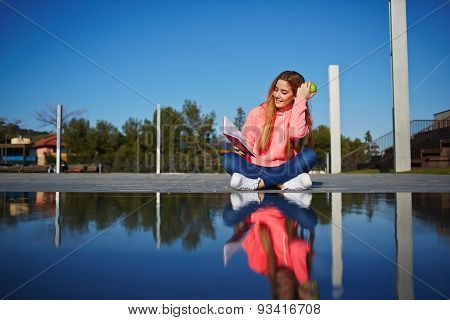 Portrait of female teenager reading absorbing book and eat green apple while sitting in the park