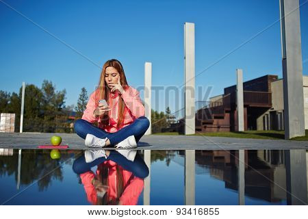 Beautiful young girl sitting at the fountain in good sunny day holding a mobile phone