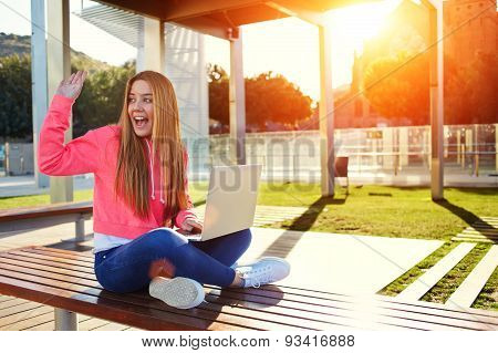 Student sitting on a bench near the university with an open laptop and waved his classmate