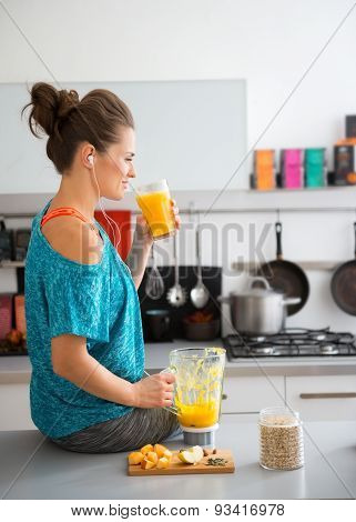 Woman In Workout Gear On Kitchen Counter Drinking Smoothie