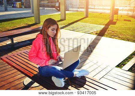 Portrait of a young girl sitting on a bench outdoors and holding an kneeling open white notebook