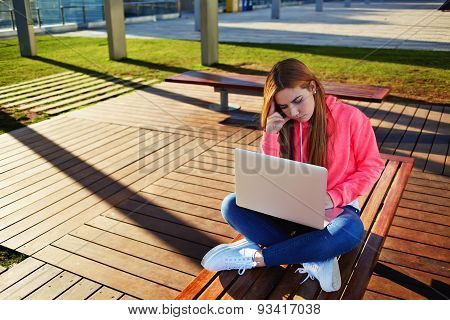 Freelancer working in the internet on their projects sit outside in the park and holding a laptop