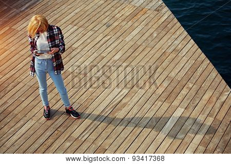 Young female using digital tablet computer standing on wooden pier outdoors