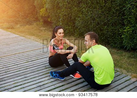 Beautiful sport couple resting after workout sitting in beautiful park