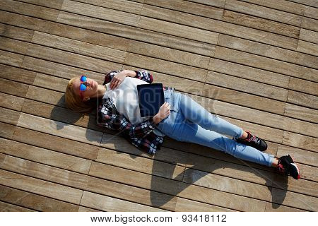 Portrait of a young attractive girl lying on the wooden floor with a tablet enjoying vacation