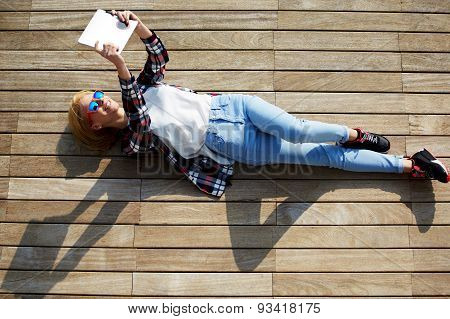 Young woman pouting for a self-portrait while lying on wooden jetty enjoying the sun