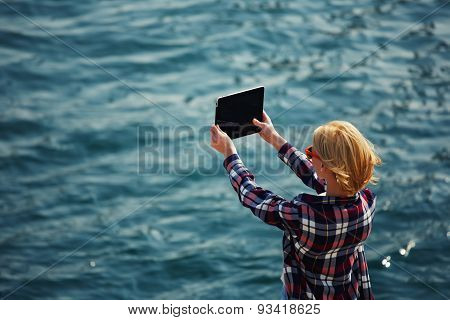 Tourist taking picture with a digital tablet camera standing against sea background on the beach