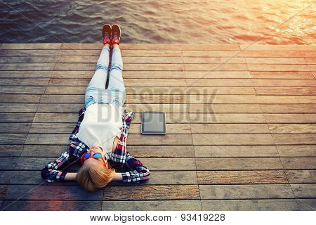 Portrait of a young tourist with tablet lying on a wooden pier and enjoy the noise of the sea