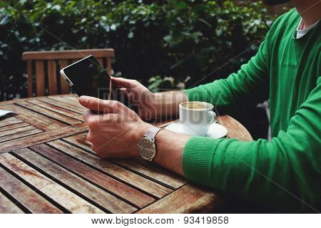 Side view freelancer sitting on the terrace with cup of coffee and touch screen tablet