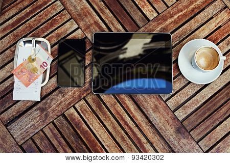 Mock-up with touch screen digital tablet smart phone bill check with money and cup of coffee