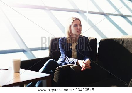 Young student sitting in big bright cafe for a cup of coffee after training at the university