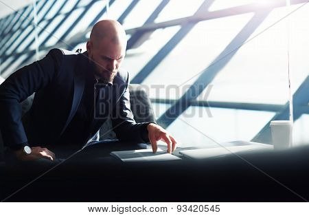 Young businessman sitting near a large window in his office and working with paper documents