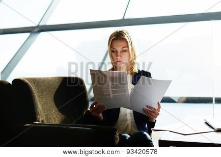 Portrait of attractive businesswoman reading papers or documents sitting in luxury coffee shop