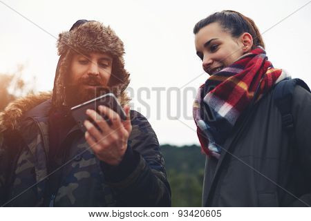 Portrait beautiful young active couple of hikers  laughing while looking to the mobile screen.