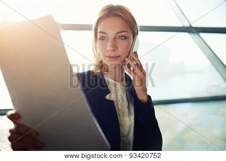 Portrait of young lovely business woman having cell phone conversation while examining paperwork.