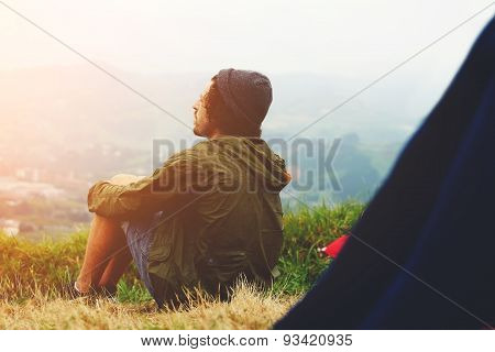 Young hike hipster man sitting at his campsite on the top of hill while enjoying the nature