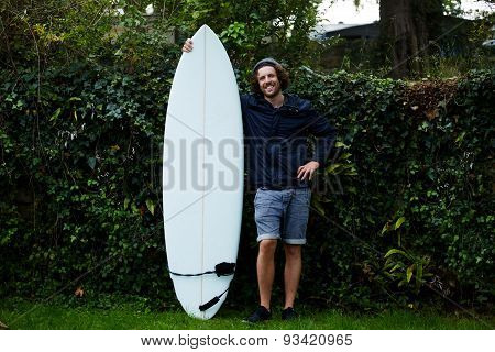 Portrait of happy young man with beard holding his surfboard standing on green hedge background