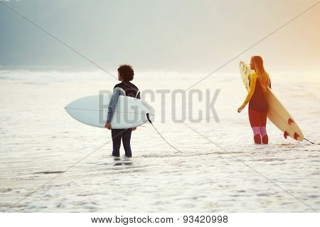 Rearview shot of a young couple standing in the water with their surfboards looking out at the ocean