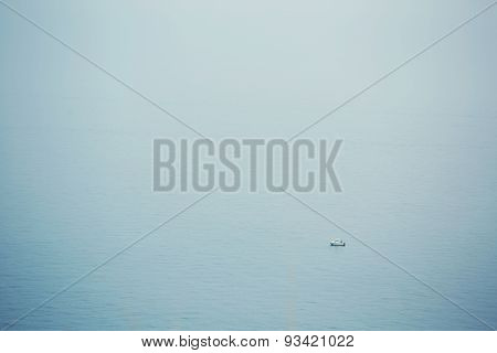 Alone boat ship in foggy sea single sail on a calm blue sea